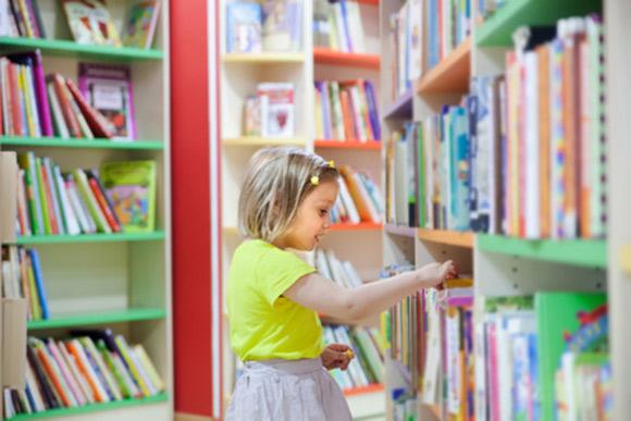 Niña eligiendo libro en una biblioteca infantil