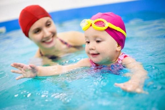 Niña aprendiendo a nadar con su mamá en la piscina