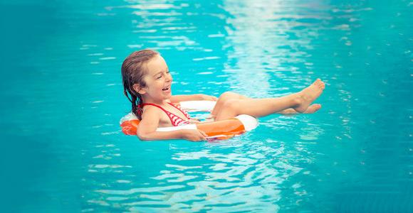 Niña jugando en la piscina con un flotador