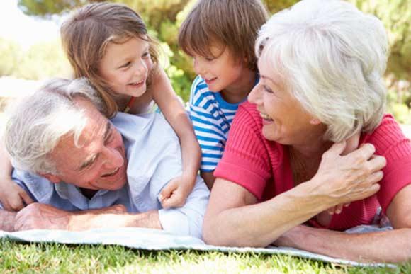 Nietos y abuelo jugando sobre el césped