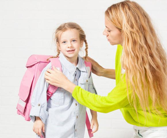 Mamá ayuda con la mochila  a su hija  para empezar en la Escuela Infantil
