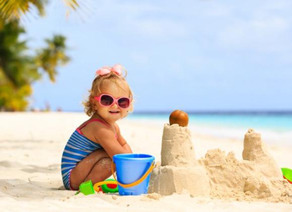Niña haciendo castillo de arena en la playa