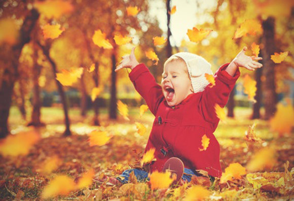 Niña jugando con las hojas en el parque