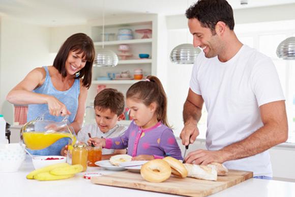 Familia preparando un desyuno con fruta cereales y lácteos