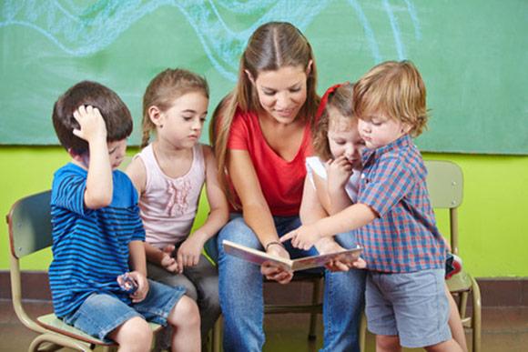 Maestra de educación infantil leyendo un libro con niños alrededor