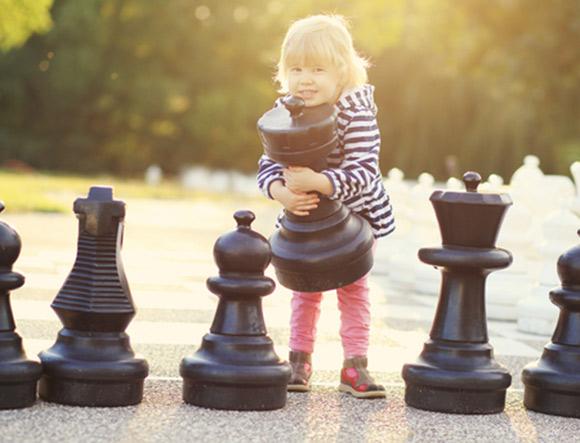 Niña colocando enormes piezas de ajedrez