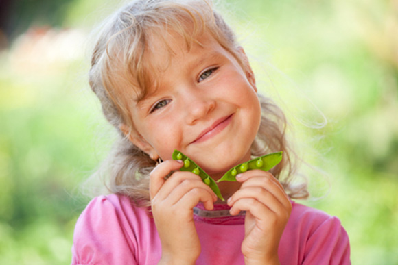 Niña sonriente vaina de guisantes al aire libre