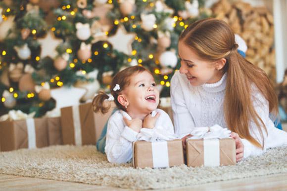 Mamá e hija con regalos de Navidad delante del árbol navideño