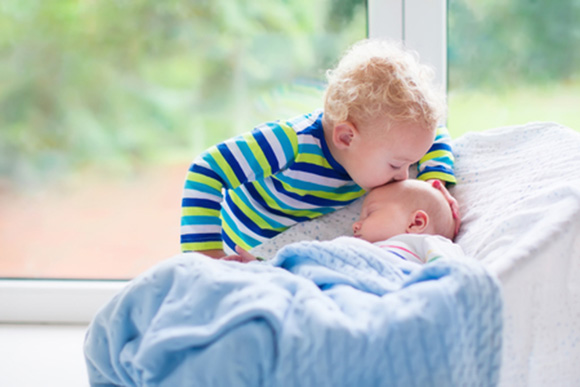 Niño besando a su hermano recién nacido