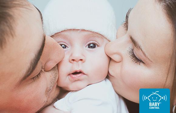 Bebé recibiendo un beso de sus padres