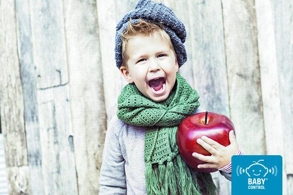 Niño con gorro y bufanda sujetando una manzana