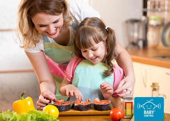 Madre y niñas cocinando salmón en la cocina