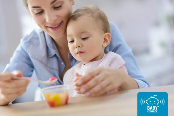 Mamá dando ensalada de frutas a su bebé