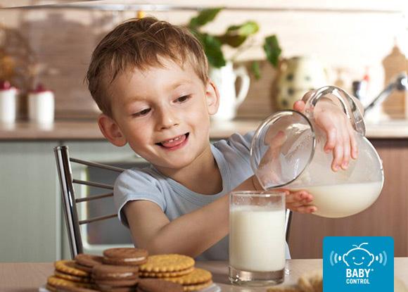 Niños sirviéndose un vaso de leche con galletas