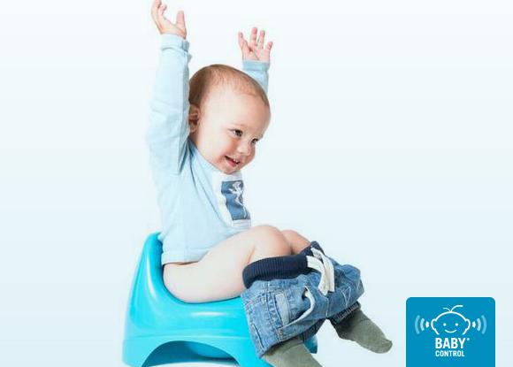 Bebé alegre con los brazos en alto sentado en un orinal