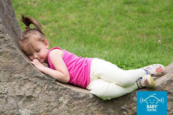 Niña tumbada sobre una piedra con fondo de césped