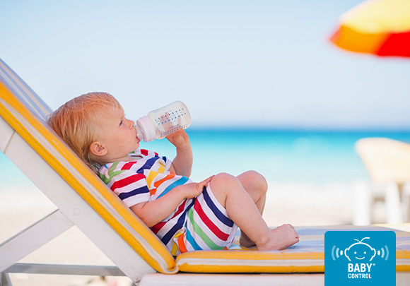 Bebé frente al mar bebiendo un biberón de agua debajo de una sombrilla