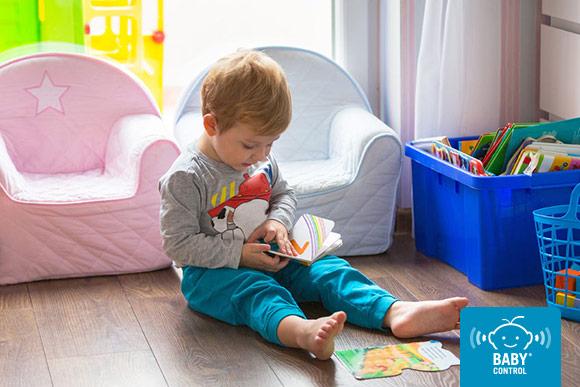 Niños manipulando un cuento sentado en su habitación