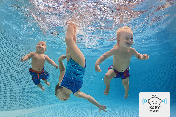 Niños jugando mientras bucean en la piscina