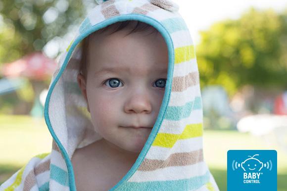 Bebé con toalla de capucha después de baño en la piscina