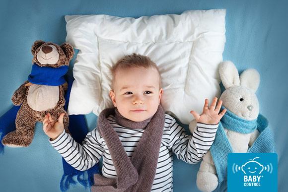 Niño con bufanda rodeado de peluches con bufanda en la cama