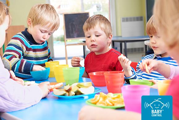 Niños pequeños comiendo solos en la escuela infantil