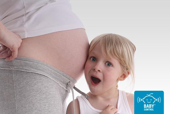 Niña escuchando la barriga embarazada de su mamá