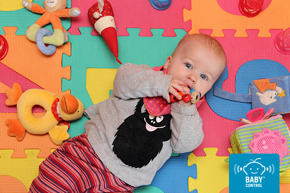 Bebé tumbado con juguetes adecuados