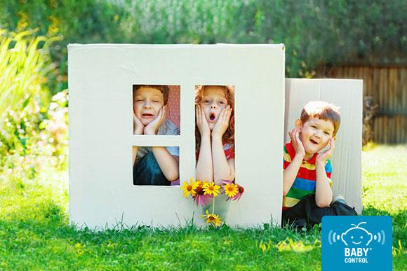 Niños jugando en una casita de cartón en el jardín
