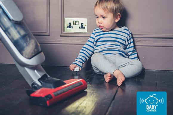 Bebé mirando una aspiradora en casa