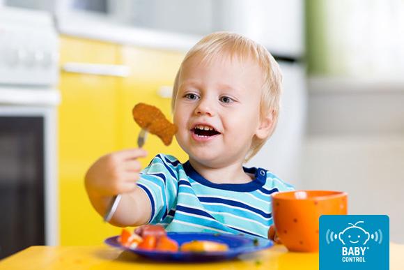 Niño comiendo croqueta de merluza con forma de pez