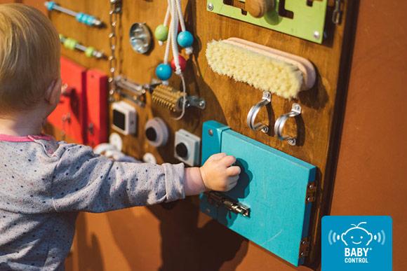 Bebé manipulando diferentes objetos de la vida cotidiana sobre un panel