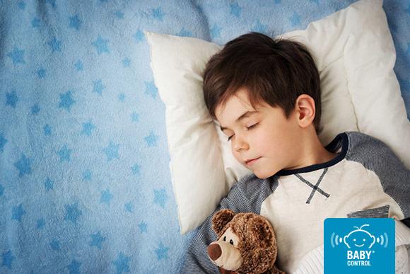Niño durmiendo con osito sobre sábanas de estrellas azules