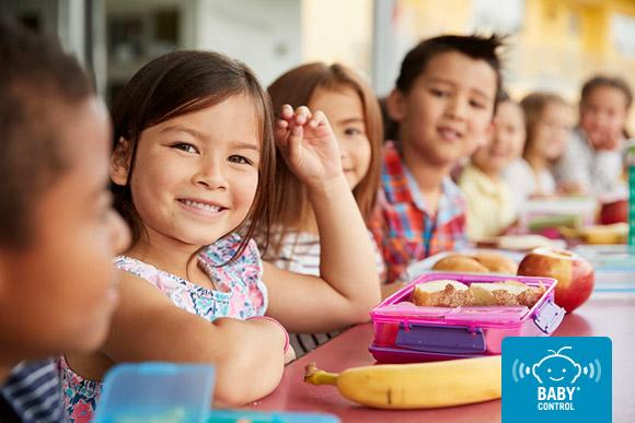 Niños en la escuela infantil con friambreras y fruta