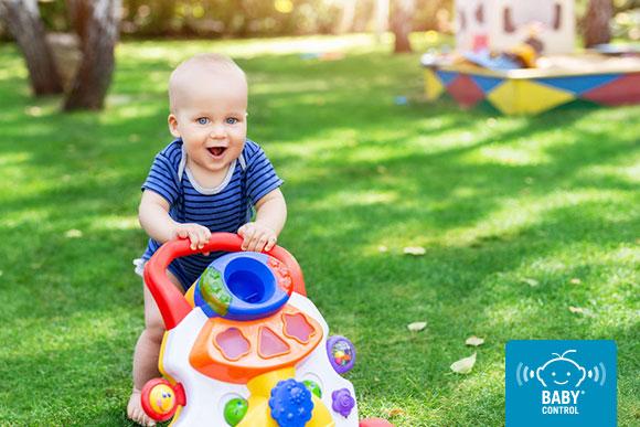 Bebé empujando andador de juguete en el jardín