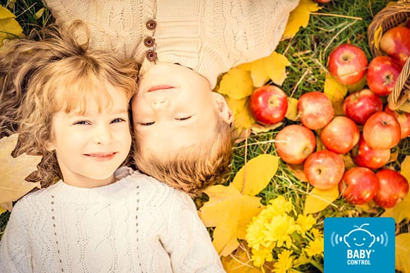 Niña y niño tumbados entre hojas amarillas y manzanas