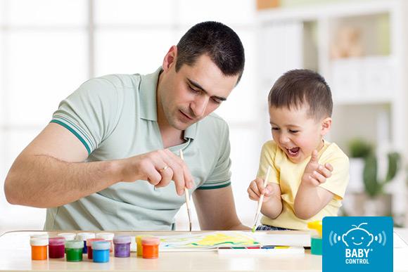 Papá divirtiéndose pintando con su hijo en casa