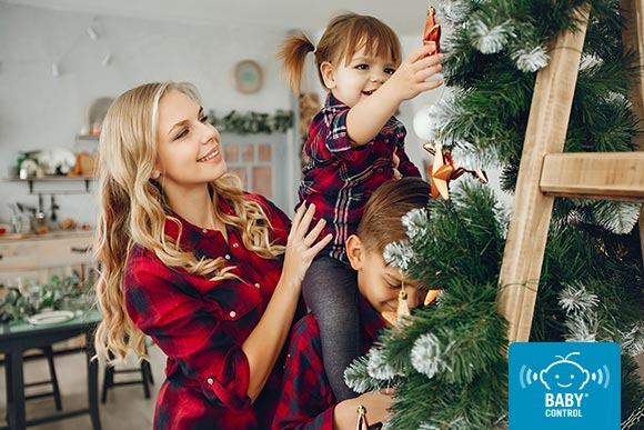 Niña colocando bola en el árbol de Navidad con su mamá y hermano