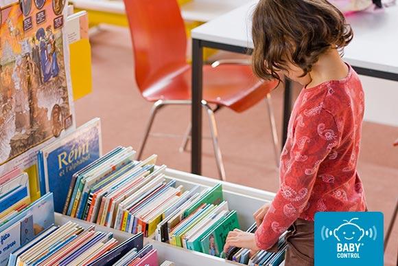 Niña mirando libros en la escuela infantil