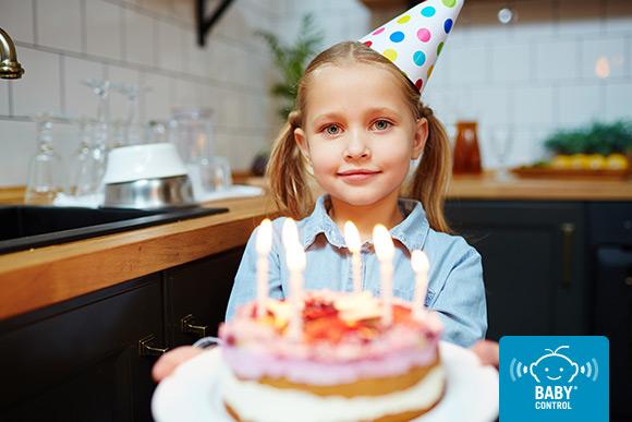 Niña llevando una tarta con velas