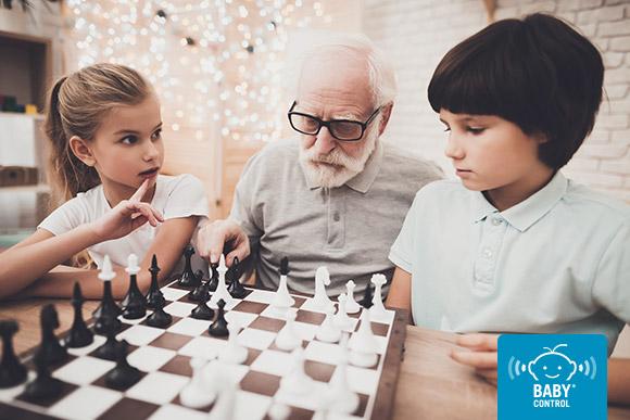 Niña y niño jugando con abuelo al ajedrez