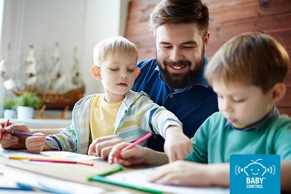 Papá sonriente mirando los dibujos que hacer sus hijos