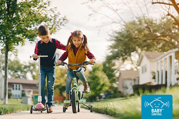 Niño con patinete y niña con bicicleta por un parque