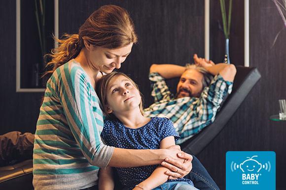 Madre abrazando y hablando con su hija en casa