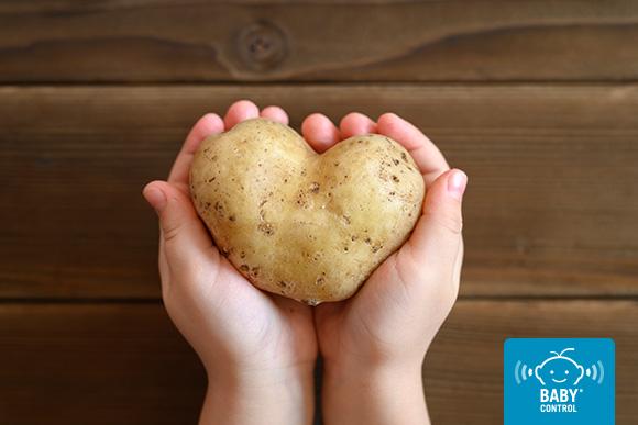 Manos de niño sosteniendo una patata con forma de corazón