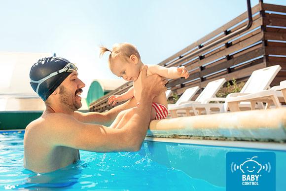 Papá jugando en el borde de la piscina con su bebé