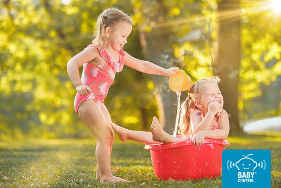 NIñas jugando con agua en un bareño a la sombra en verano