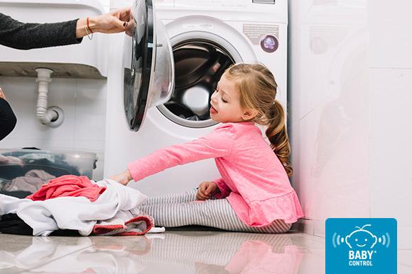 Niña con ropa cerca de la lavadora