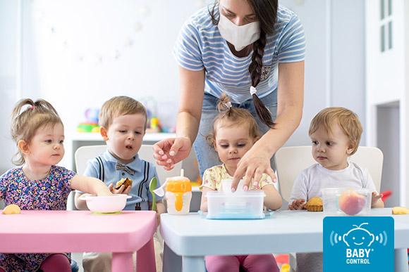 Niños con su tutor en la hora del almuerzo de la Escuela Infantil