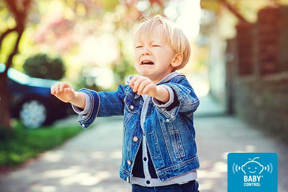 Niño llorando al aire libre levantando las manos hacia sus padres